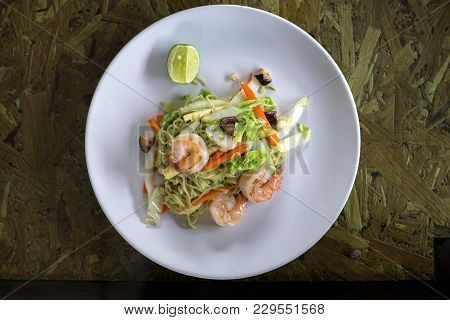 Stir Fried Noodles With Shrimp, Cabbage, Carrot, Corn And Mushroom In White Plate On Wooden Table, T