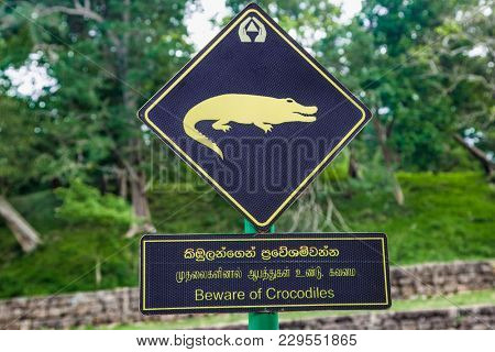 Beware of crocodiles. Caution plate alerting about dangerous predators in water of canals at Sigiriya, Sri Lanka.