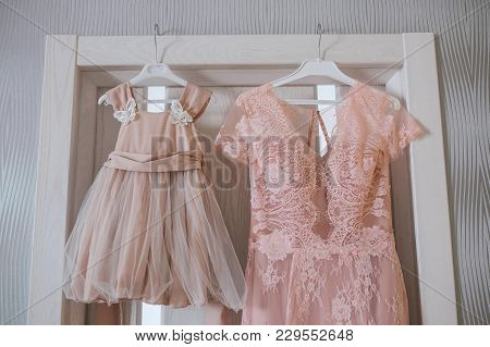 Evening Pink Wedding Dress With Lace On The Hanger And Beside Baby Beautiful Beige Tulle Dress. Hori
