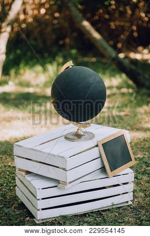 A Black Globe With A Slate Stands On Wooden Pallets On The Grass. Wedding Original Decor. Vertical