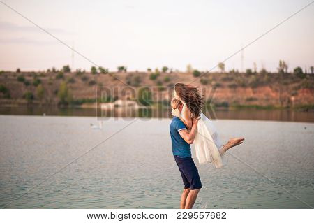 Happy Couple In The Sunset Embraces In The Water. A Man Raises A Woman In Her Arms And Turns Her Aro