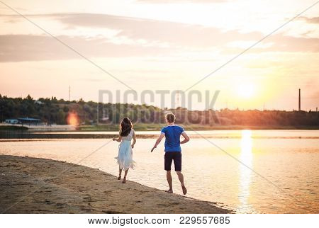 A Happy Couple On A Sunset Background Running On The Water. A Man Runs After A Woman In A Dress On A