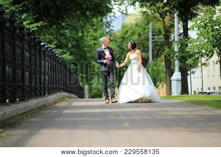 Newlywed Bride And Groom Walking Outdoors In Wedding Clothing After Ceremony
