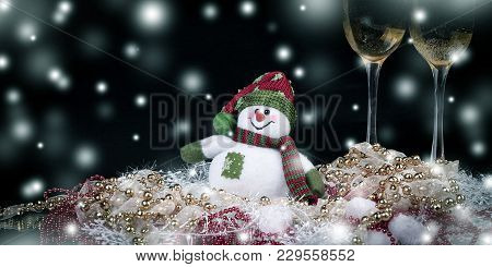 Fun Toy Snowman And Two Glasses Of Champagne On A Black Background.photo With Copy Space