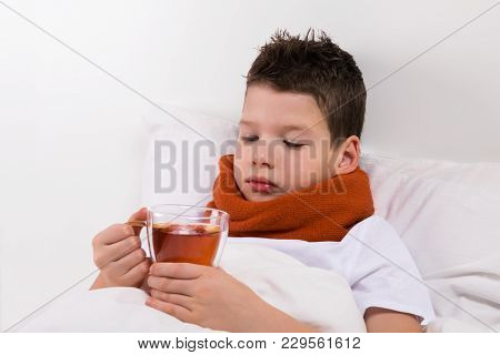 The Boy Drinks Tea On The Bed With A Throat Disease