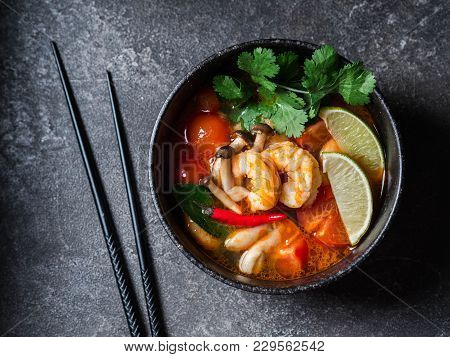 Traditional Thai Food Cuisine. Tom Yum Spicy Soup In Black Bowl On Grey Background. Thai Food Concep