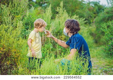 Father And Son Use A Spray From An Allergy Because Of An Allergy To Ragweed.