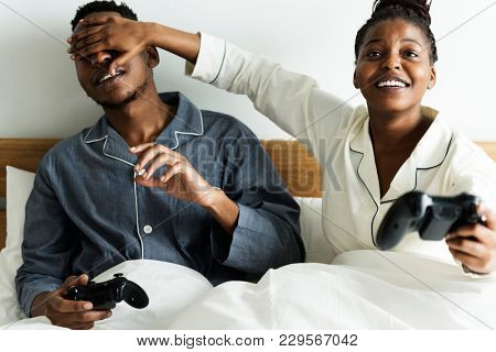 A happy couple playing video game in bed