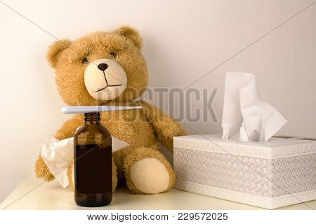 Plush bear is sick, has  rhinitis and temperature.Plush bear with thermometer, MEDICINE bottle and paper tissues. poster