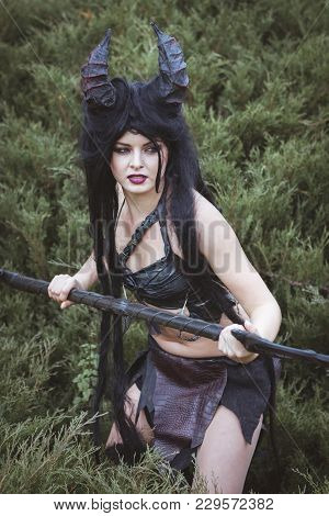 Beautiful Brunette In A Savage Costume Holds A Spear In Her Hands.
