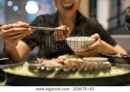 Woman's Hand Use Chopsticks Hold Korean Pork Grilled, Pork Slice Roasted, Bbq Or Yakiniku.happy Smil