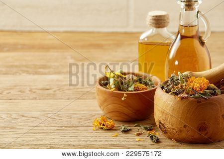 Picturesque Composition Of Oil Jars, Pestle And Mortar With Motley Grass Over Wooden Background, Sel