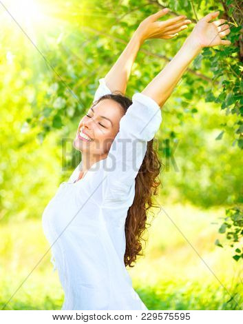 Beautiful Young Woman Enjoying nature Outdoor. Happy and Healthy Smiling brunette Girl with healthy smile relaxing in the Summer Park,  Breathing fresh air. Sunny day. Health care concept
