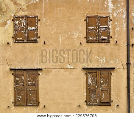 An Old Italian Rugged Building Facade With Cracks And Ruined Wooden Blinds. Traditional Old Italian