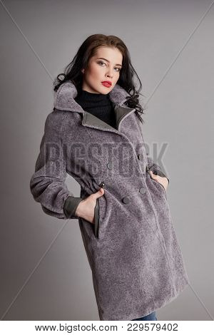 Woman In Spring, Autumn Coat Fashion On A Gray Background In The Studio, Spring Clothes. Bright Coat