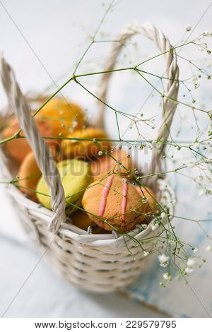 Macaroons In A White Basket On A Light Wooden Background.