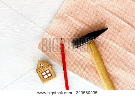 Flat Layout With A Wooden House, Hammer, Pencil On A Background Of Millimeter Paper Top View / Resid