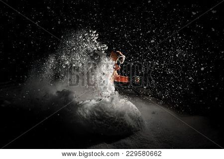 Freeride Snowboarder Dressed In The Orange Sportswear And Glasses Jumping In Powder Snow At Night