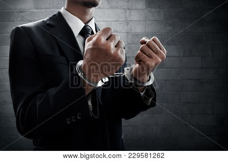 Business Man In Handcuffs On Wall Background
