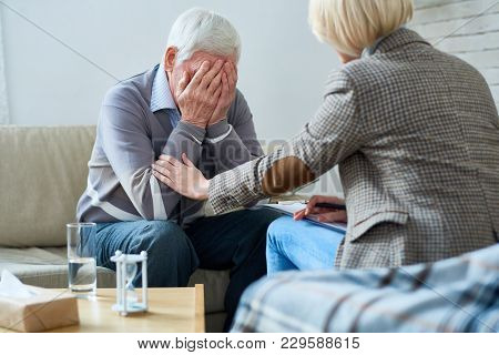 Portrait Of Depressed Senior Man Crying During Therapy Session With Female Psychiatrist Trying To Co