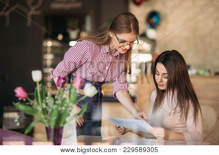 Hospitable Waitress Help To Customer What To Choose.