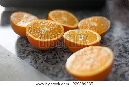 Detail Shot Of Three Oranges Sliced In Half On A Kitchen Table Ready To Be Squeezed To Extract All T