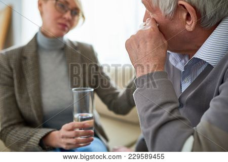 Rear View Of Crying Senior Man In Therapy Session With Female Psychologist In Background, Copy Space