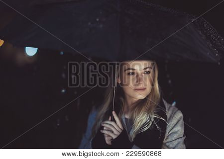 Portrait of a beautiful thoughtful woman standing alone with umbrella under the rain in dark night and with sadness thinking about something