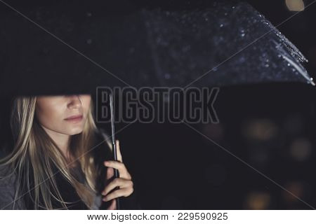 Gorgeous sad woman standing under big black umbrella on rainy night, half face, walking under downpour, loneliness and sadness concept
