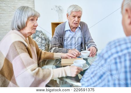 Group Of Senior People Chatting And Drinking Tea Enjoying Evening In Luxury Retirement Home, Copy Sp