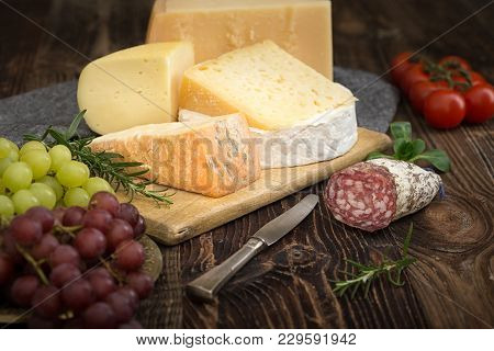 Cheeses With Basil, Rosemary, Tomatoes, Grapes And Salame.