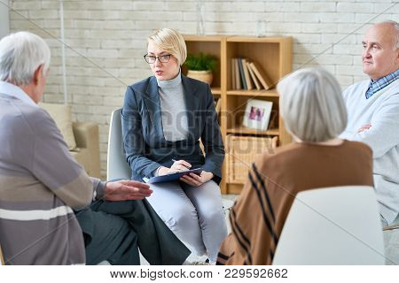 Portrait Of Blonde Female Psychiatrist Wearing Glasses Leading Group Therapy Session For Senior Peop
