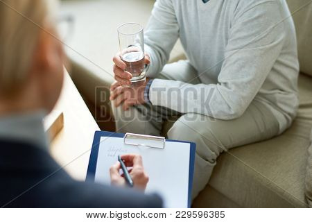 High Angle Close-up Of Female Psychologist Writing On Clipboard While Listening To Depressed Senior
