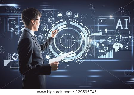 Side Portrait Of Handsome Young Businessman With Digital Business Hologram. Touchscreen And Media Co