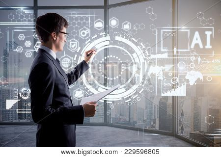 Side Portrait Of Handsome Young Businessman With Digital Business Hologram. Touchscreen And Innovati