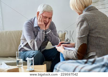 Portrait Of Depressed Senior Man Sharing Problems During Therapy Session With Female Psychiatrist Wr