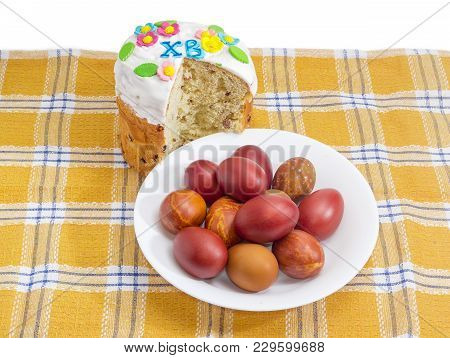 Partly Cut Easter Cake Decorated With White Icing And Colorful Sugar Decors, Dish With Easter Eggs O