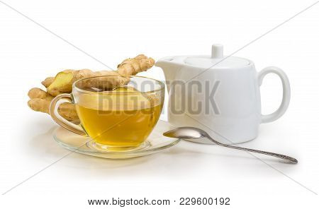 Ginger Tea In The Glass Transparent Cup On A Glass Saucer With Tea Spoon, White Porcellaneous Teapot