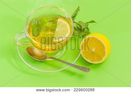Tea With Slice Of Fresh Lemon And Mint Leaf In The Glass Transparent Cup On A Glass Saucer With Tea