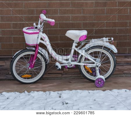 The First Snow. Children's Bicycle Under The Snow