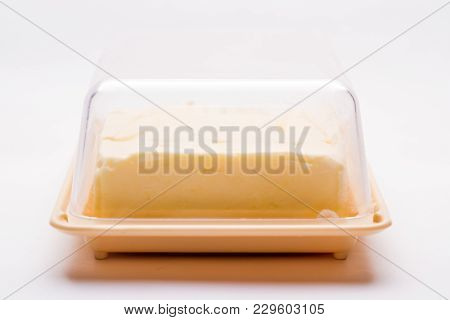 Butter In A Pink Oil Can On A White Background With A Transparent Plastic Lid
