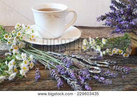 Аromatic Lavender Tea And Wild Chamomile On Wooden Background, Focus Selective