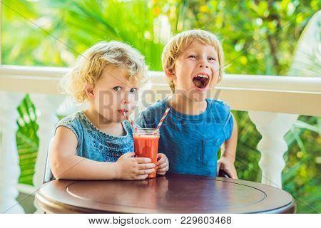 Children Boy And Girl Drink Orange Smoothie From Papaya.