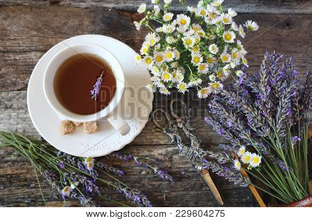 Аromatic Lavender Tea And Wild Chamomile. Top View On Wooden Background, Focus Selective