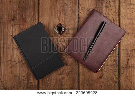 An Overhead Photo Of A Black Book, A Leather Journal, An Ink Well And Pen, Shot From Above On A Dark