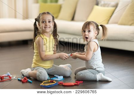Conflict Between Little Sisters Playing At Home. Kids Are Fighting, Toddler Girl Takes Toy, Sibling