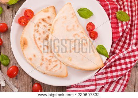 Cascione Italian Flatbread With Cheese On White Dish.