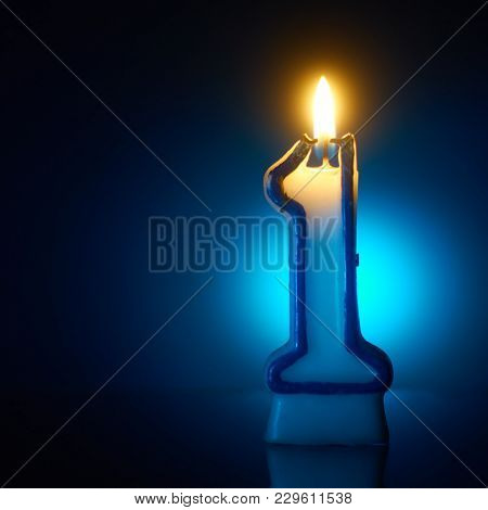 Number One - Burning birthday candle on blue background