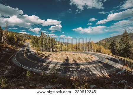Highway with hairpin turn (switchback) at autumn sunny day in Rocky Mountain National Park. Colorado, USA.
