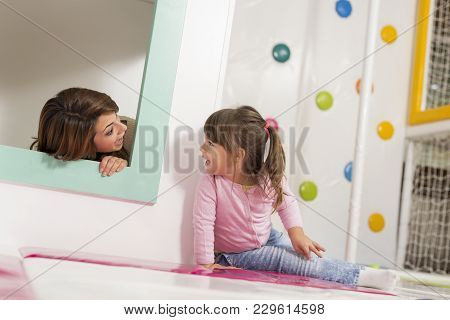 Mother And Daughter Playing In A Playroom, Hiding In A Small Wooden House, Playing Hide And Seek